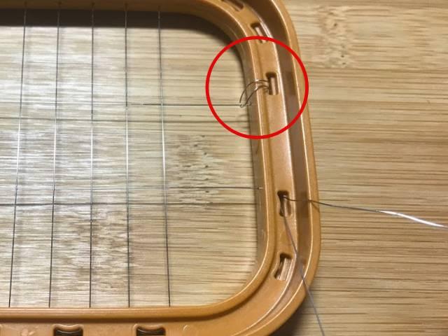穴から引っ張り出した針金を、引っ張る対象のワイヤーにくぐらせ、再び枠の穴に戻す