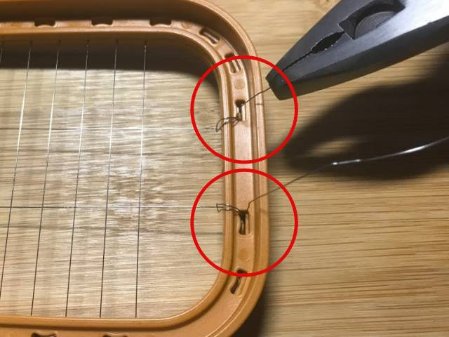 隣のワイヤーもくぐらせ、再び枠の穴に戻す